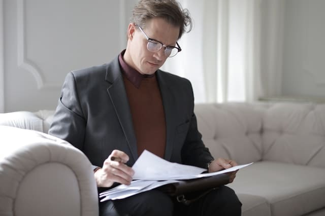 Classy Executive Male Reading Papers On Couch 3760514 - Auster Inteligência Contábil