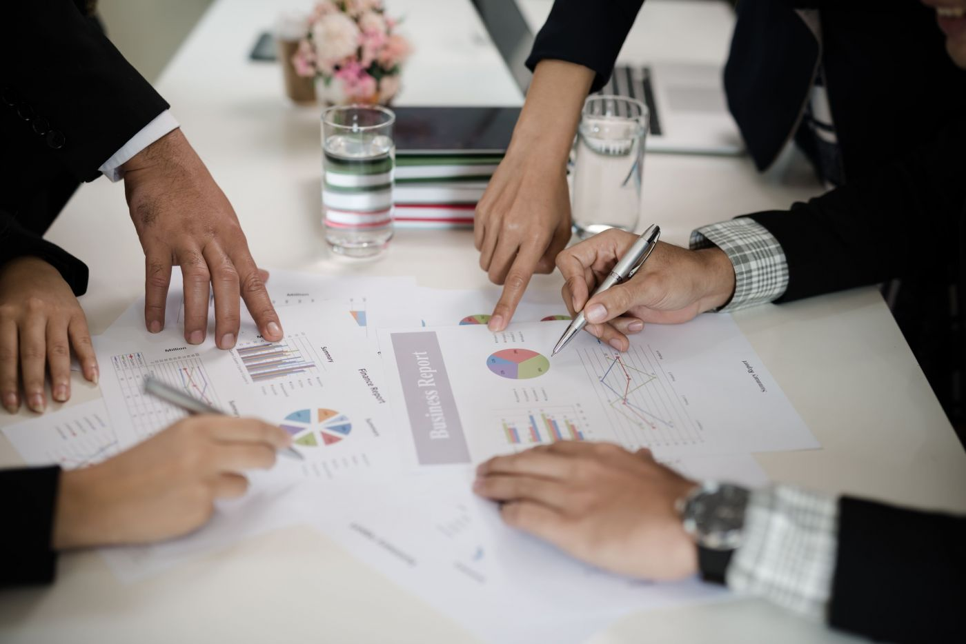 Foto aproximada de uma mesa de reunião, onde aparecem mãos escrevendo e folhas com gráficos em cima da mesa