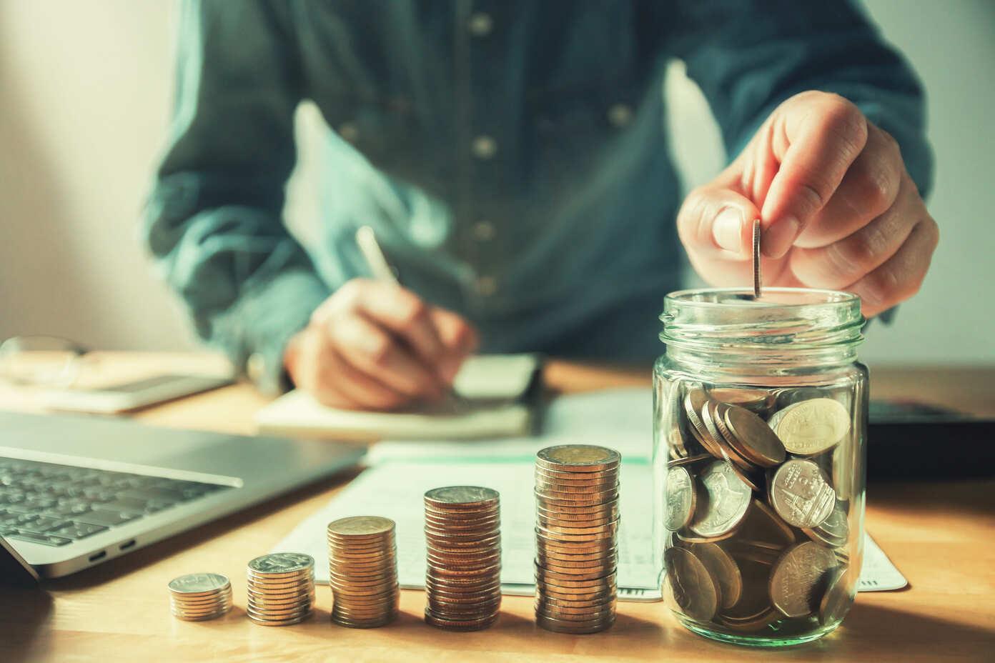 Imagem de um homem depositando uma moeda em um pote com mais moedas, ao lado dele tem mais pilhas de moedas