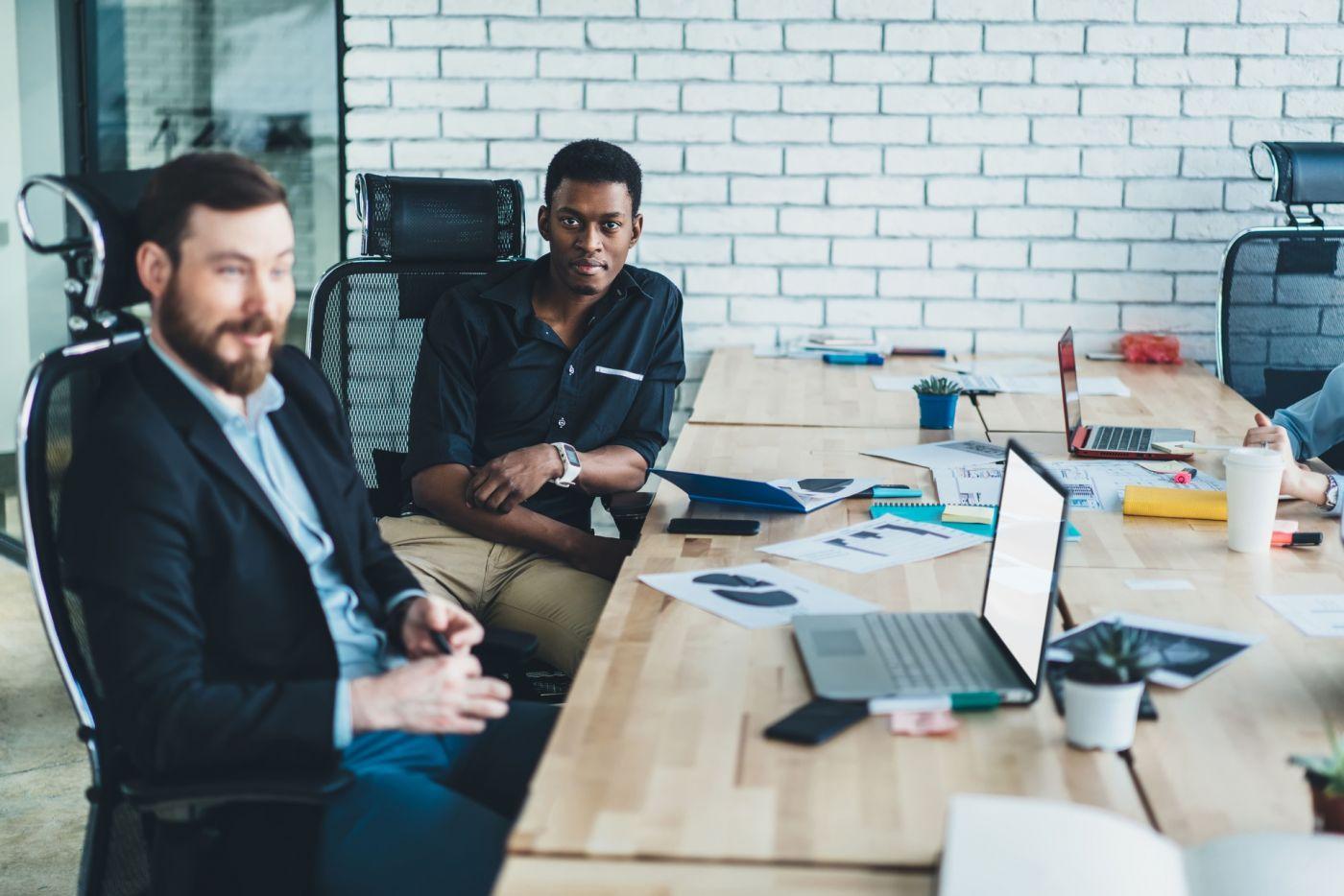 Imagem de dois homens sentados à mesa, em uma sala de reunião
