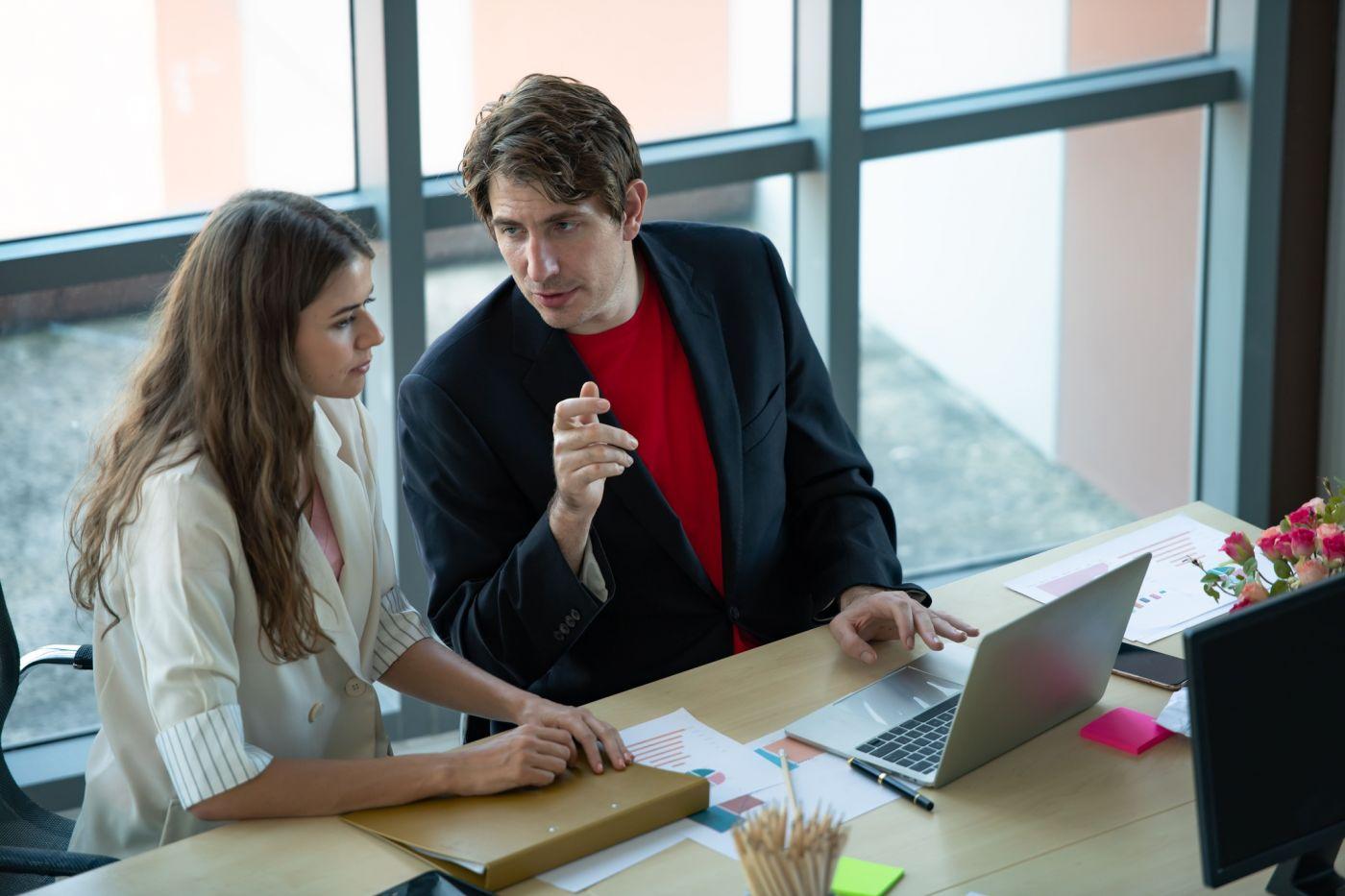 Homem passando instruções de trabalho, em frente à um notebook, para uma mulher