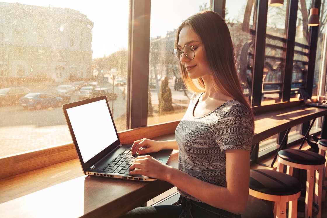 Foto de uma mulher trabalhando em frente à um notebook