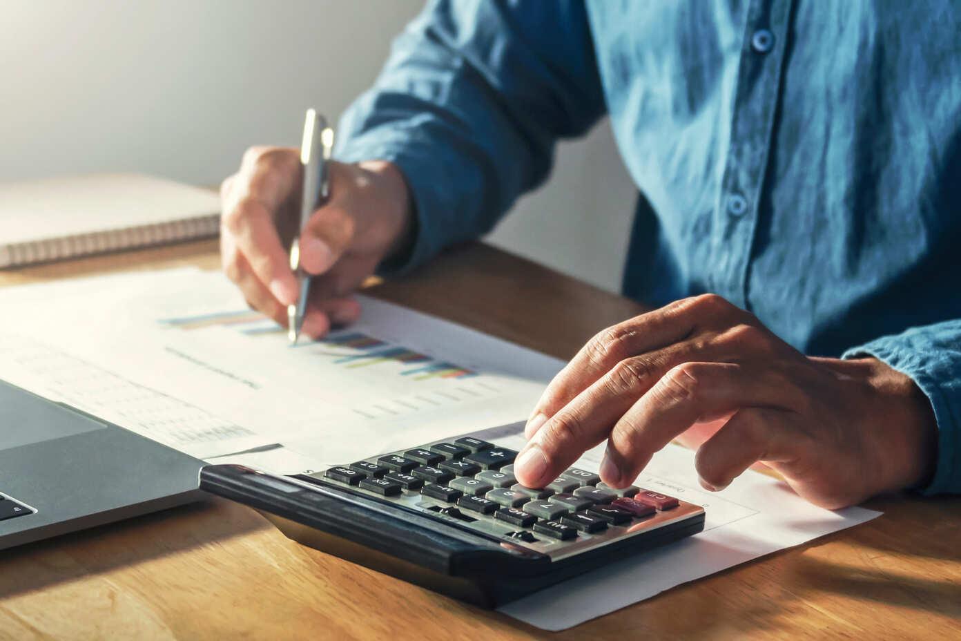 Imagem de um homem fazendo contas em uma calculadora com uma mão e segurando uma caneta na outra