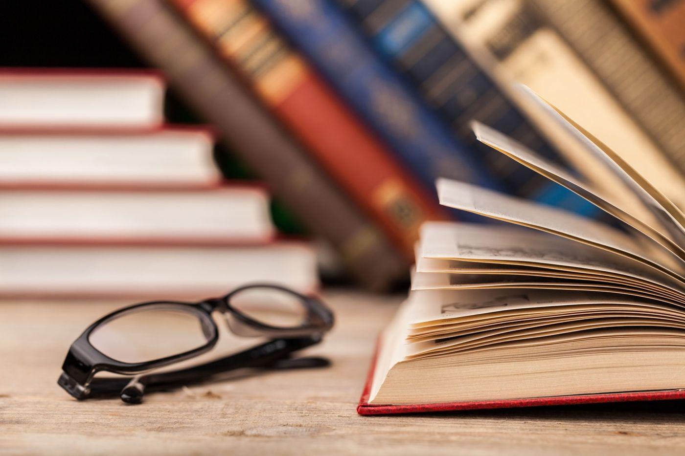 Foto de um livro aberto e um óculos ao lado